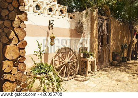 Ethnic Style Patio With Oriental Touches, Large Wooden Wheel And Potted Plants. Afternoon Siesta In