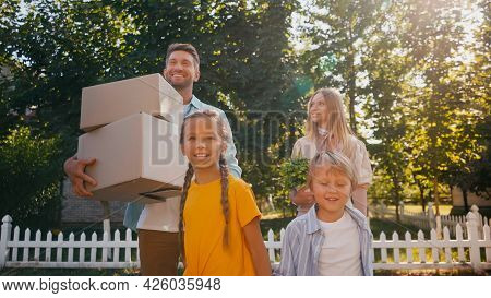 Happy Parents Holding Boxes And Plant While Walking With Kids, Relocation Concept.