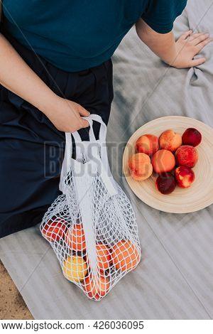 Female Hand Holding White Mesh Bag With Fruits Sitting On Sand. Eco Friendly Picnic, Reusable Shoppi