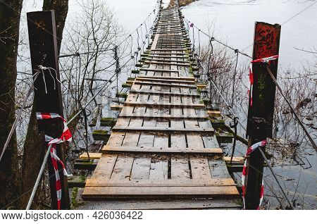 Wooden Suspension Bridge For Walking. Bridge In A Spring Forest