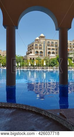 Summer Resort With Arabic Style Buildings. Luxury Vacation Scene With Nobody At Pool Rippled Water.