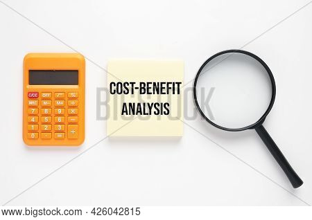 Calculator, Magnifying Glass And Notepad Wirtten Cost-benefit Analysis. Cost-benefit Analysis Is A S