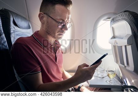Young Man Using Mobile Phone At Airplane. Passenger Enjoys Flight With Internet Connection A Beverag