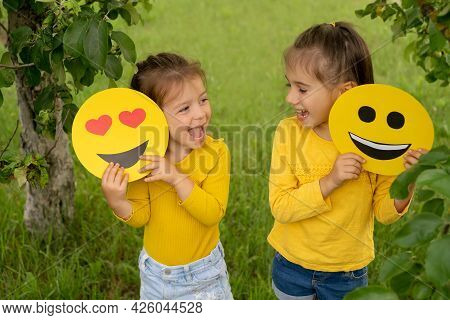Two Little Funny Girls Are Holding Smile Faces With Different Emotions In Their Hands. Children Are
