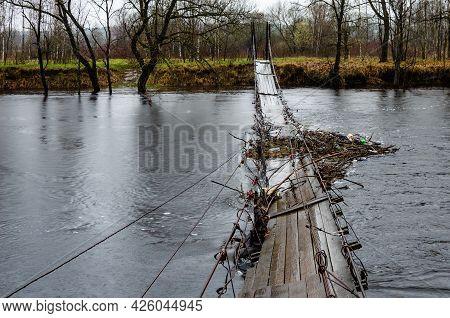 Suspended Wooden Bridge Over A River. The Water Level In The River Has Risen Suspension Bridge Traps