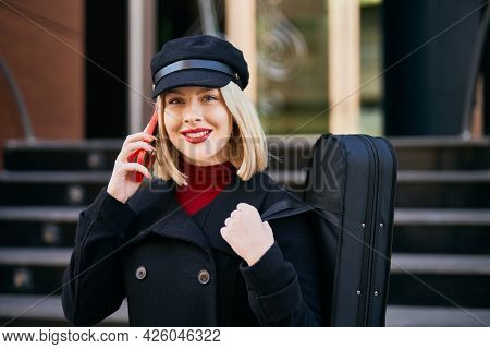 Young blonde musician woman talking on the smartphone at music academy.