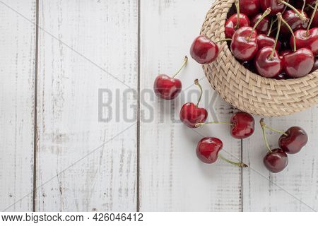 Summer Background With A Basket Of Cherries On A Wooden Background, Sweet Ripe Red Berries Are Scatt