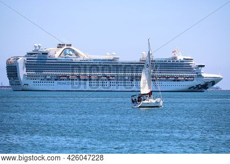 July 6, 2021 In Long Beach, Ca:  Sail Boat Sailing Besides The Princess Cruise Ship In The Long Beac