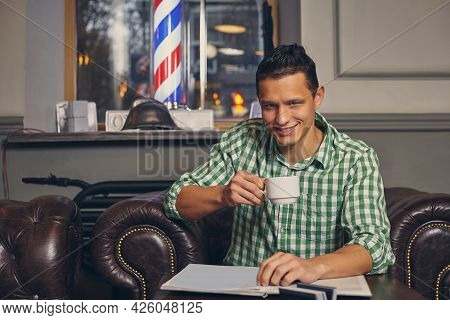 Handsome Young Man In A Barbershop Is Waiting For The Master In The Waiting Room While Drinking Coff