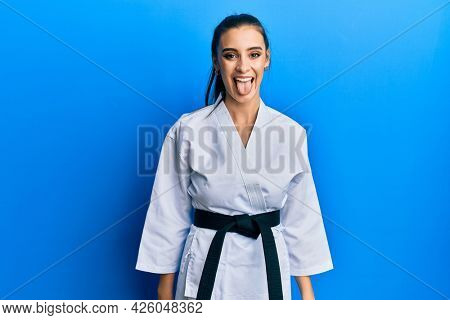 Beautiful brunette young woman wearing karate fighter uniform with black belt sticking tongue out happy with funny expression. emotion concept.