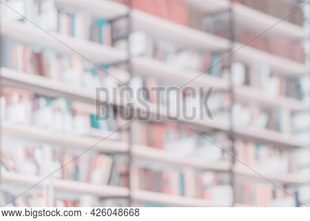Blurred Light Background Of Rows Of Books On Bookshelfs, Bookshop, Library. Concept Of School, Back