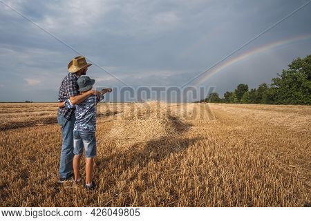 Father And Son Are Standing In Their Wheat Field After Successful Harvest. They Are Looking At Rainb