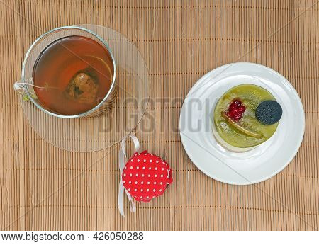 Traditional English Cup Of Green Tea In A Glass Cup With Cake On Ceramic Plate