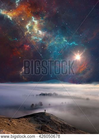 Man Silhouette Standing On Rock With Misty Fog, Distant Hill, Nebula And Sun. Photo Manipulation Wit