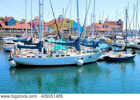 July 6, 2021 In Long Beach, Ca:  Sailboats And Yachts Docked With Colorful Colonial Style Buildings