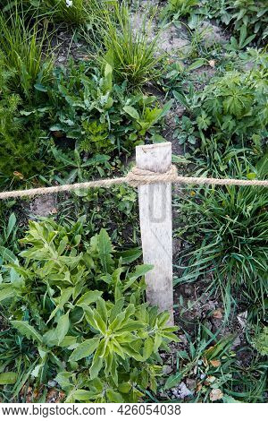 Flowerbed Limiter Made Of Rope And A Wooden Peg. Concept Of Using Natural Materials