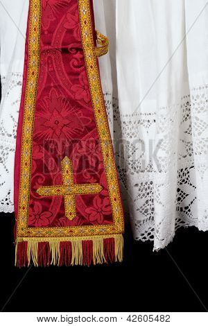 Antique red maniple hanging over the lace edge of an old priest surplice