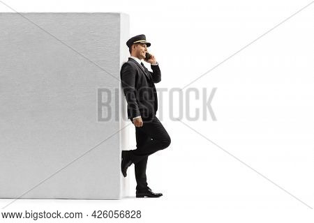 Full length profile shot of a chauffeur leaning on a wall and using a mobile phone isolated on white background
