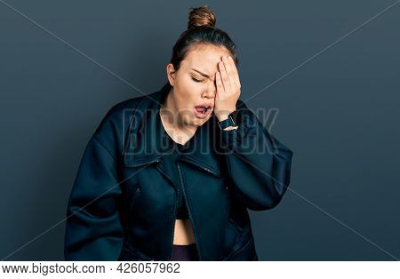 Young hispanic girl wearing sportswear yawning tired covering half face, eye and mouth with hand. face hurts in pain.