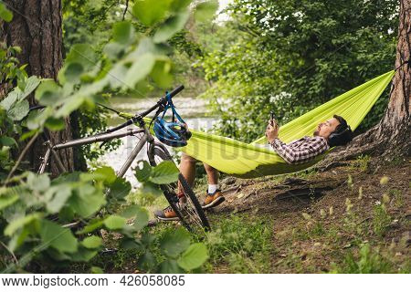 Man On Bicycle Trip At Camping By Lake Is Relaxing In Green Hammock While Listening To Music. Active