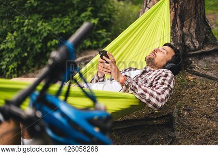 Man Travels On Bicycle, Relaxing In Green Hammock, Surfing Internet On Smartphone, Listening Music O