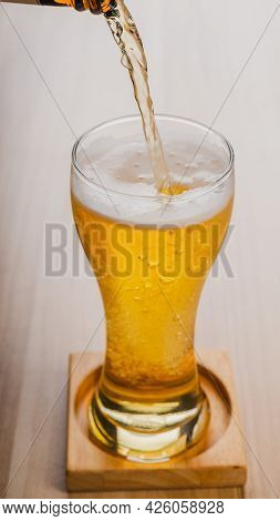 Filling Glass Glasses Of Light Beer, Cold Craft Beer In A Glass On Wood Table