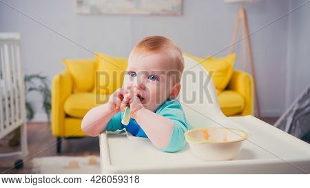 Infant Boy With Blue Eyes Sitting In Feeding Chair And Sucking Spoon Near Bowl