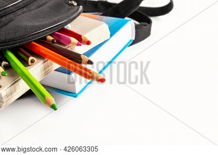 Open School Backpack On An White Background. Books, A Notebook And Pencils Are Sticking Out Of An Op