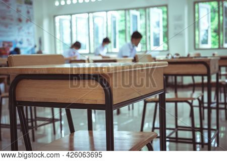 Class Room Tables And Chairs With Paper Documents Of Exam Test On Desk In Examination School While B