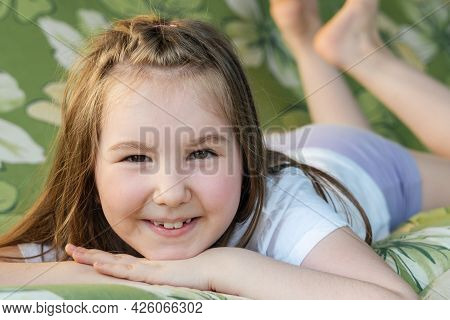 Portrait Of A Little Beautiful Smiling Girl. Little Cute Girl Having Fun And Rest Outside In Summer.