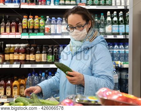 April 24 2021, Russia, Moscow. A Caucasian Woman Picks Cucumber Vegetables At The Grocery Store. A W
