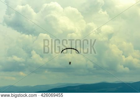 Silhouette Of A Paraglider Flying In The Cloudy Sky. Extreme Sport. Extreme Vacation.