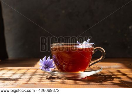 A Glass Mug With A Chicory Drink. A Blue Chicory Flower Floats In A Cup With A Drink