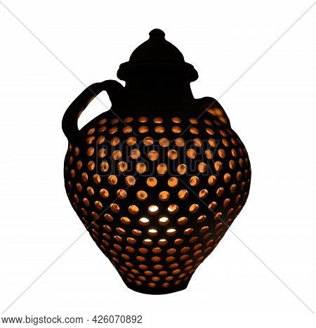 Pot With Light Inside It And Holes Over White