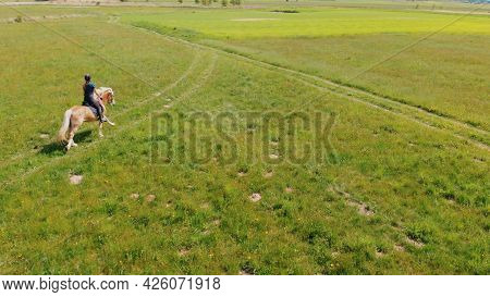 Aerial View Of A Female Jockey On A Light Brown With A Blonde Mane Moving Across The Farm Field. Rid