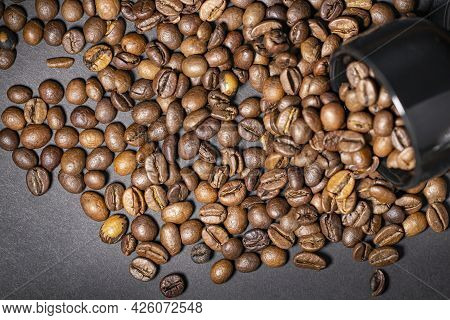 Coffee Beans Scattered On Black Background And Black Ceramic Cup With Beans