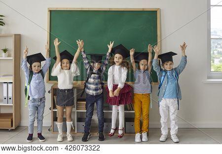 Funny Little Kindergarten Or Junior High School Graduates Who Are Dressed In Mortar Boards.