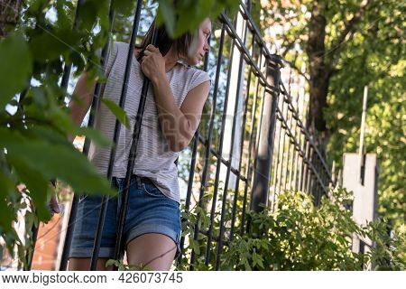 Curious Woman Climbed Into A Private, Protected Area, She Penetration Through A Wrought-iron Fence A
