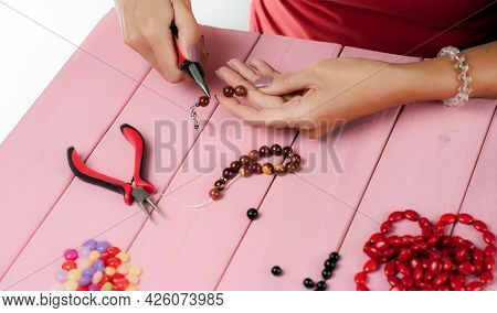 Jewelry Making. Making A Bracelet Of Colorful Beads. The Girl With The Tools In The Hands Of Manufac