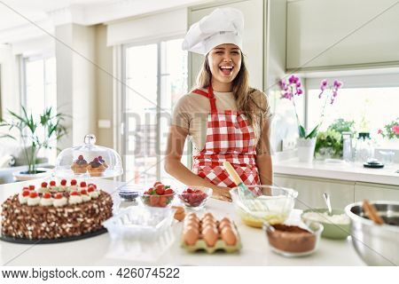 Beautiful young brunette pastry chef woman cooking pastries at the kitchen winking looking at the camera with sexy expression, cheerful and happy face.