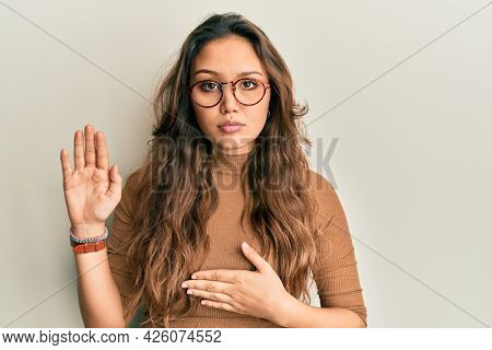 Young hispanic girl wearing casual clothes and glasses swearing with hand on chest and open palm, making a loyalty promise oath