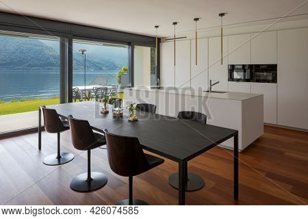Interior of a modern apartment, kitchen and dining room stand together. The floors are in a luxury and very precious parquet, the kitchen is white. In short, a super design architecture.