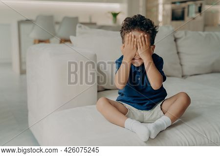 Small Excited Boy In Tshirts And Shorts Playing Game Of Hide And Seek, Covering Face With His Hands,