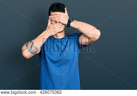 Young hispanic man wearing casual t shirt covering eyes and mouth with hands, surprised and shocked. hiding emotion