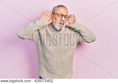 Handsome senior man with beard wearing casual sweater and glasses trying to hear both hands on ear gesture, curious for gossip. hearing problem, deaf