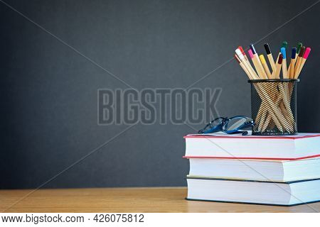 A Stack Of Books, Glasses, Many Pencils In The Metal Holder On The Wooden Background Of A Black Scho