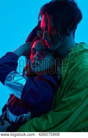 Side View Of Male Teenager In Stylish Outfit Embracing Young Girlfriend Under Neon Illumination Agai