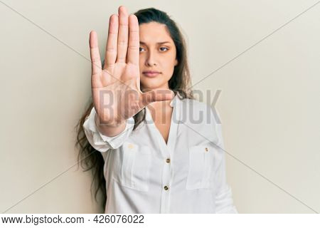 Beautiful middle eastern woman wearing casual clothes doing stop sing with palm of the hand. warning expression with negative and serious gesture on the face.