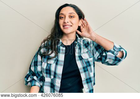 Beautiful middle eastern woman wearing casual clothes smiling with hand over ear listening and hearing to rumor or gossip. deafness concept.