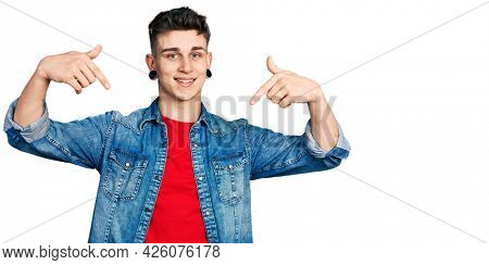 Young caucasian boy with ears dilation wearing casual denim jacket looking confident with smile on face, pointing oneself with fingers proud and happy.